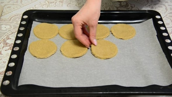 Thumbnail for Woman Puts Raw Oatmeal Cookies on a Baking Sheet