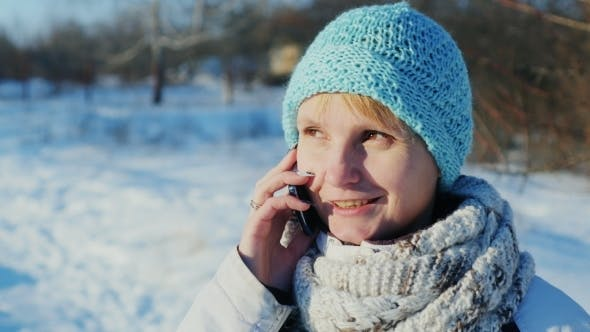 Cover Image for Attractive Woman Talking On a Cell Phone In The Winter Park