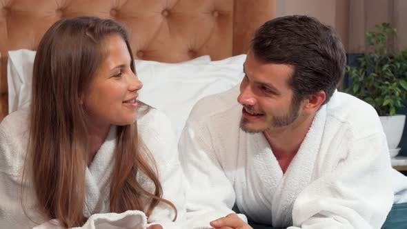 Thumbnail for Happy Loving Couple Talking Lying in Bed Together Wearing Bathrobes