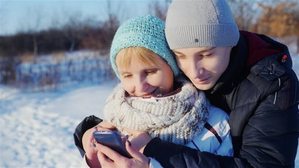 Cover Image for Mother And Son Read From The Screen Of The Smartphone, Smiling