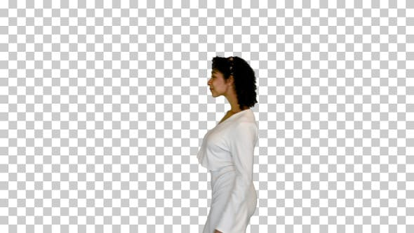 Young black lady in white walks adjusting hair, Alpha Channel