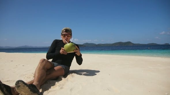 Thumbnail for Man On The Beach Drinking Coconut Juice