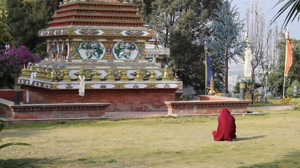 Thumbnail for Man With His Head Wrapped In a Robe Sits In Front Of Buddhist Stupa