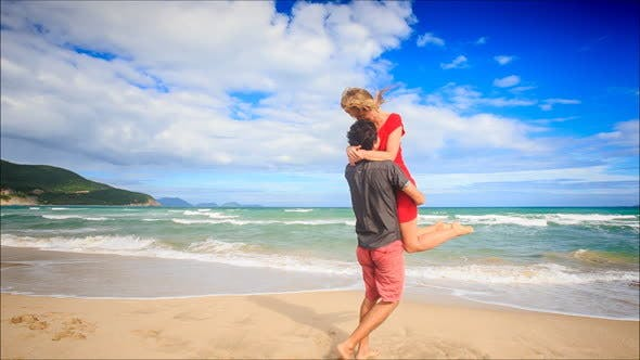 Thumbnail for Guy Holds in Arms Circles Kiss Blond Girl on Beach Wave Surf