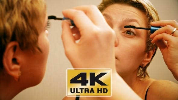 Cover Image for Pretty Blond Woman Applying Mascara Make-up