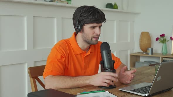 Man Is Speaking in Microphone in Studio Recording Podcast Gesturing Expressing Opinions for Online