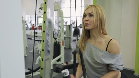 Thumbnail for A Muscular Woman Athlete Performs Triceps Strain on Hand in The Gym.