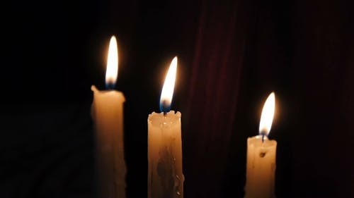 three burning Christmas candles on a dark background. the occasion.