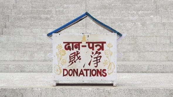 Cover Image for Girl Puts Money In The Donation Box