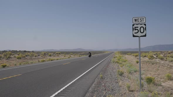Thumbnail for Motorcycle Drives Along A Road In The Desert 1