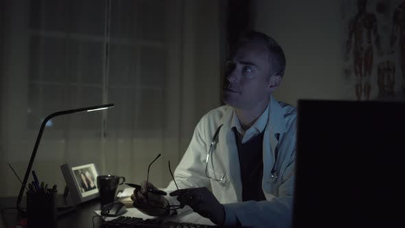 Thumbnail for Serious Doctor Working At His Office Desk