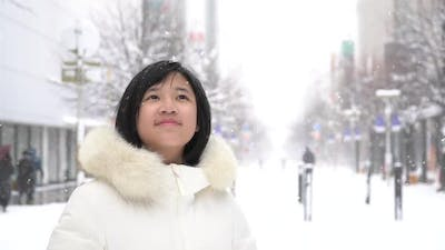 Portrait Of Beautiful Asian Girl Enjoying Snowfall
