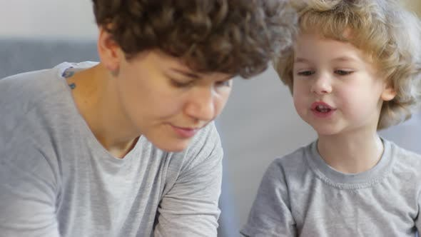 Cover Image for Adorable Kid Speaking with Mom while Making Xmas Paper Crafts