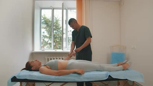 Osteopath Treatment - the Doctor Massaging Fingers of Young Woman