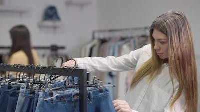 Young Caucasian Millennial Woman Choosing Jeans Pants in Shop Indoors