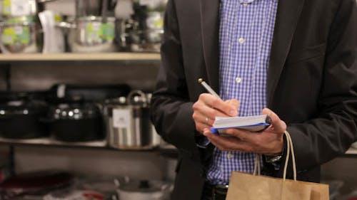Mann in einem Notizbuch mit einer Einkaufsliste