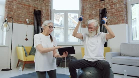 Thumbnail for Old Man doing Exercises with Dumbbells and Repeating Exercises that His Positive Wife