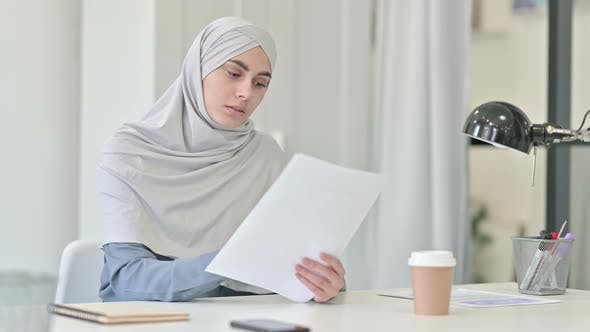 Young Arab Woman Reading Documents in Office
