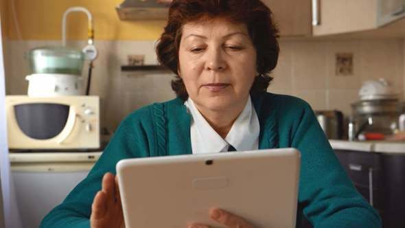 A Mature Woman Is Using A Tablet PC At Home