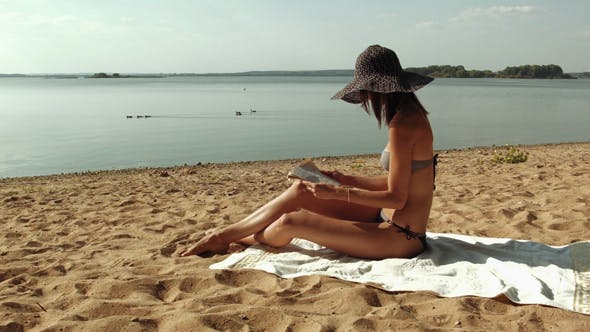 Thumbnail for Young Woman Reading Book At The Beach
