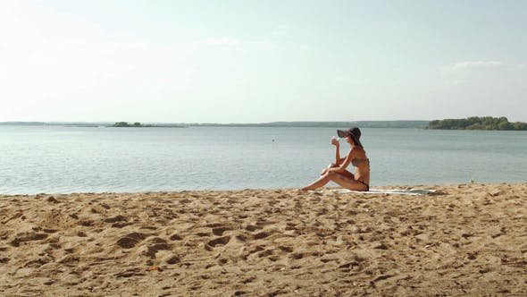 Thumbnail for Young Woman Drinking On The Sand Near the Sea