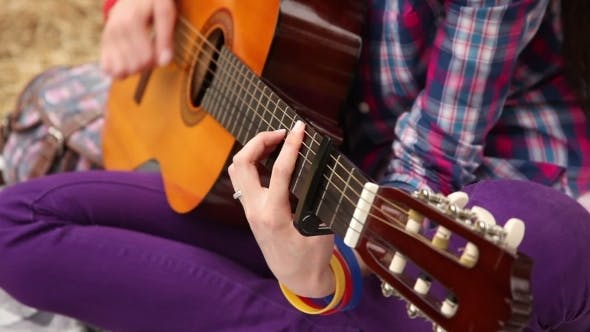 Girl Composes Music With a Guitar
