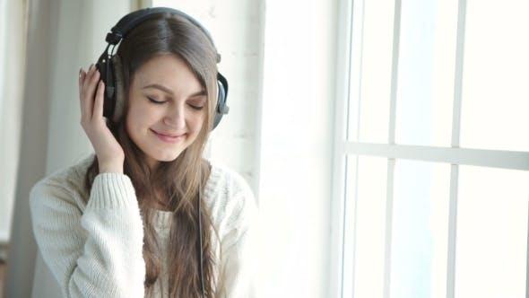 Thumbnail for Woman Listening Music In Headphones On Windowsill Background