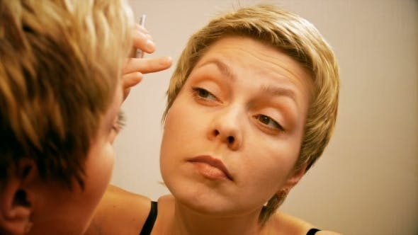 Thumbnail for Woman Plucks And Pulls Her Eyebrows Out At Mirror
