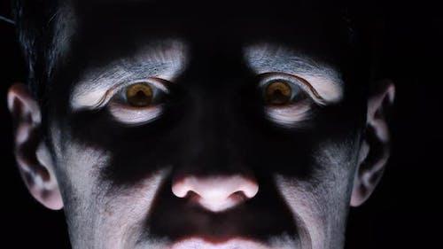 Vampir blickt im Dunkeln auf die Kamera