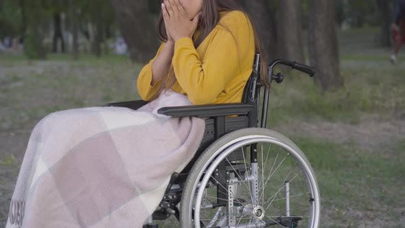 Thumbnail for Young Unrecognizable Paraplegic Woman Sitting on Wheelchair in Park and Thinking. Caucasian Disabled