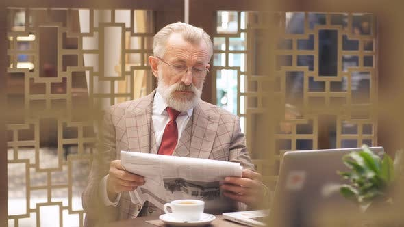 Thumbnail for Old Businessman with Laptop at Coffee Break in His Office Concept