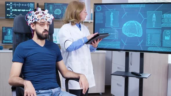 Female Neurologist Reading Data From Brainwave Scanning Headset