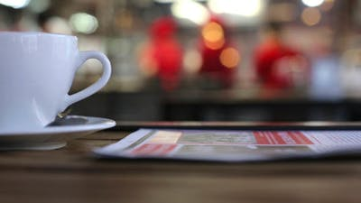 Cup and a Newspaper in a Cafe