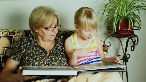 A Girl With Her Grandmother Looking Photo Album