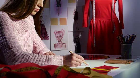 Thumbnail for Designer Draws a Sketch in the Background Is a Mannequin with a Red Dress. Close Up
