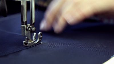 Woman Sews Clothes In a Sewing Workshop