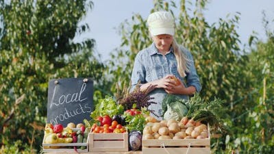 A Small Farmer Puts Vegetables on the Farmer's Market Counter