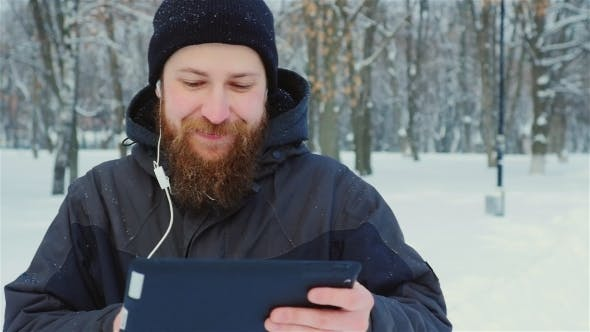 Cover Image for Bearded Man Uses Tablet In Winter Park