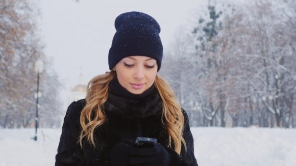 Cover Image for Attractive Woman Uses a Smartphone, Is In The Winter Park
