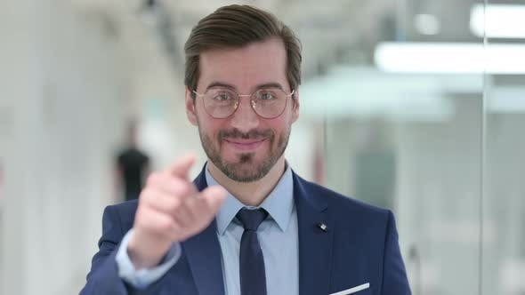 Thumbnail for Portrait of Assertive Young Businessman Pointing with Finger and Inviting