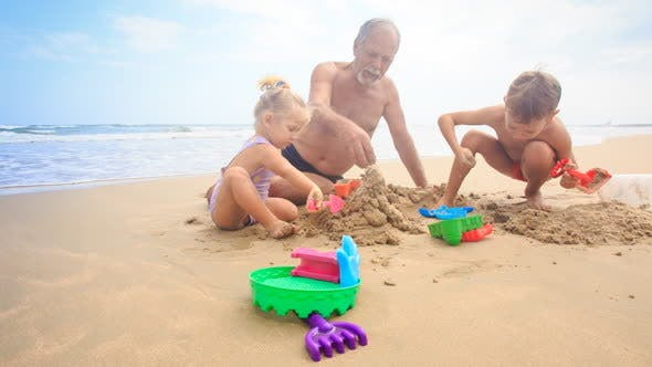 Thumbnail for Grandpa Kids Build Sand Castle on Beach by Wave Surf