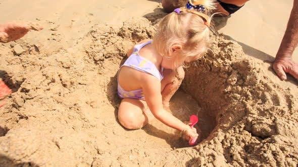 Thumbnail for Grandpa and Kids Play among Sand Heap on Beach