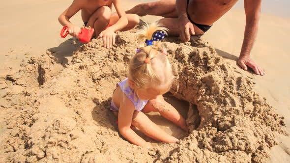 Thumbnail for kleine Mädchen spielt in sand Loch von Opa Boy auf Strand