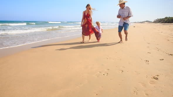 Thumbnail for Little Girl Mother in Red Grandpa Run by Foamy Surf along Beach