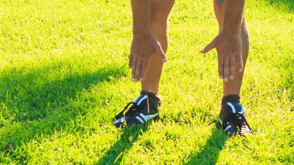 Thumbnail for Man Does Morning Exercises Bends to Feet on Green Grass Lawn