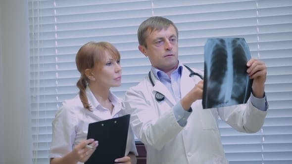 Thumbnail for Two Doctors Examining Patients X-rays In Hospital