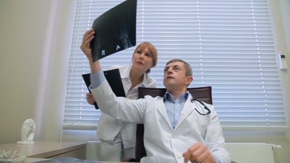 Thumbnail for Two Doctors Examining Patients X-rays In Office