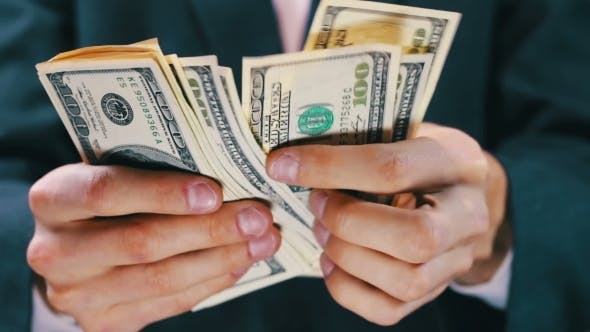 Cover Image for Businessman Counts Money In Hands.