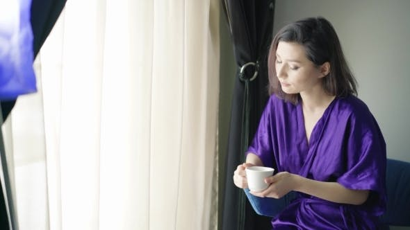 Thumbnail for Young Woman At The Window With a Cup Of Coffee