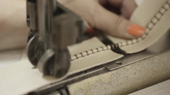 Thumbnail for Worker Makes Seams On Leather Material By Sewing Machine In Factory.